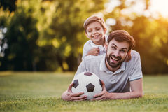 Dad with son playing baseball. Handsome dad with his little cute sun are playing baseball on green grass lawn Royalty Free Stock Image