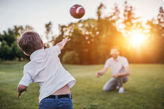 Dad with son playing baseball. Handsome dad with his little cute sun are playing baseball on green grass lawn Royalty Free Stock Images
