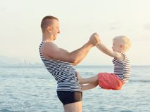 Dad and son are playing on the beach. Fun pastime.  Stock Images
