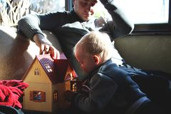 Dad and son are playing in the doll house stock photography
