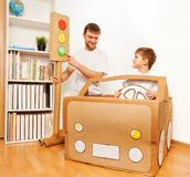 Dad and son playing drivers with cardboard car Stock Photography