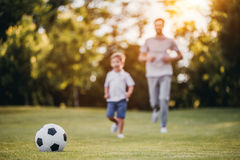 Dad with son playing football. Handsome dad with his little cute sun are having fun and playing football on green grassy lawn Stock Photography