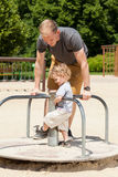 Dad and son playing on merry-go-round Stock Photography