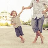 Dad and son playing near a house Stock Image