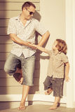 Dad and son playing near a house Stock Photo