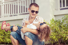 Dad and son playing near a house at the day time. Stock Photography