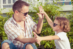 Dad and son playing near a house at the day time. Concept of friendly family Royalty Free Stock Photography