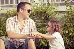 Dad and son playing near a house at the day time. Concept of friendly family Royalty Free Stock Photos