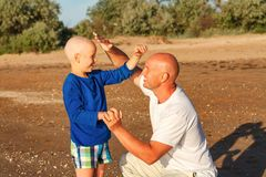 Dad and son playing by the sea, happy family royalty free stock photography