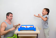 Dad and son playing table hockey Royalty Free Stock Image