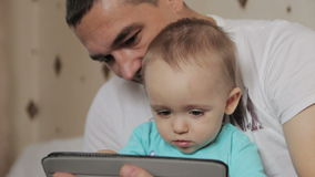 Dad and  son playing on tablet stock footage