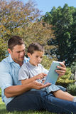 Dad and son playing with a tablet pc in a park Stock Photos