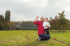 Dad and son playing. Dad playing with son throwing a paper airplane royalty free stock photo
