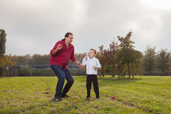 Dad and son playing. Dad playing with son throwing a paper airplane royalty free stock photos
