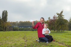 Dad and son playing. Dad playing with son throwing a paper airplane royalty free stock image
