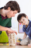 Dad and son playing with toys Stock Images
