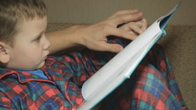 Dad and son read a book stock video footage
