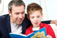 Dad and son reading a book at home. Happy father and son spending time in reading. Dad looking into the boys book Royalty Free Stock Photography