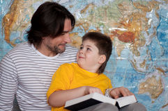 Dad and son reading  book on a map of the world Royalty Free Stock Photos