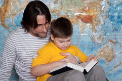 Dad and son reading  book on a map of the world Stock Photo