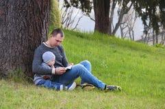 Dad and son reading a book Stock Photos