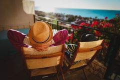 Dad and son relax on balcony terrace with sea view. Family comfort royalty free stock images