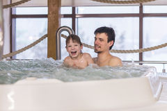 Dad and son relax in the tub. With hydro massage in Spa salon stock photography