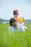 Dad and son relaxing on  grass Royalty Free Stock Photos