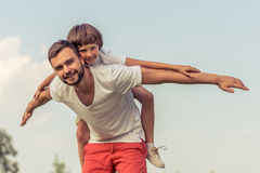 Dad and son resting outdoors Stock Images