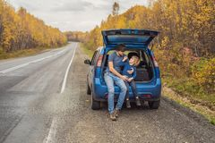 Dad and son are resting on the side of the road on a road trip. Road trip with children concept stock photography