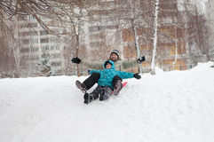 Dad and son riding from frozen hill Royalty Free Stock Photos