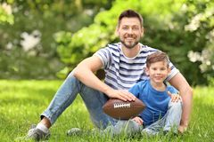 Dad and son with rugby ball. In green park royalty free stock photography