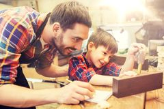 Dad and son with ruler measuring plank at workshop. Family, carpentry, woodwork and people concept - father and little son with ruler and pencil measuring wood Stock Photo