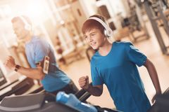 Dad and son in the same clothes in gym. Father and son lead a healthy lifestyle. A men and a boy are engaged on a treadmill. They are engaged in headphones stock images