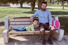 Dad and son sit on bench in park, Kashan, Iran. Kashan, Iran - April 26, 2017: Iranian man with his little son is sitting on a bench in the park royalty free stock photo