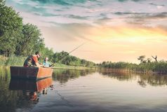Dad and son sitting in boat and fishing on lake. The boy showing his dad how he caught a fish royalty free stock photos