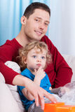 Dad and son sitting on the couch Stock Image