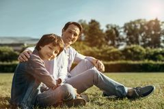Dad and son sitting on the grass smiling and hugging. Happy together. Delighted smiling hugging dad and son sitting on the grass and the boy crossing his legs stock images