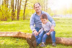 Son and father resting in the village. Dad and son sitting on a log in the meadow. toned stock image