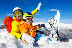 Dad and son skiers sit in snow on mountain top Royalty Free Stock Images