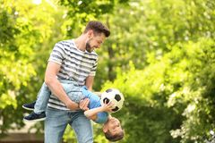Dad and son with soccer ball. Dad and son with soccer ball in green park royalty free stock image