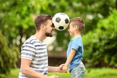 Dad and son with soccer ball. In green park stock photo