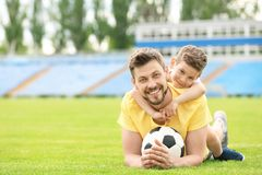 Dad and son with soccer ball. In stadium royalty free stock photos