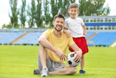 Dad and son with soccer ball. In stadium stock photos