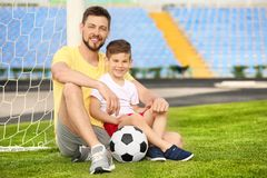 Dad and son with soccer ball. In stadium Stock Image