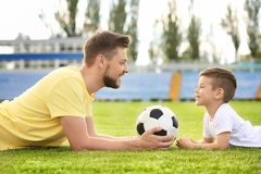 Dad and son with soccer ball. In stadium stock images