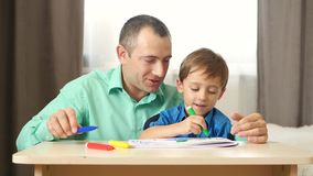 Dad and son spend time painting with colored felt pen. The concept of a happy family.