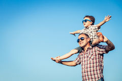 Dad and son in sunglasses playing in the park at the day time. People having fun outdoors.  Concept of friendly family Royalty Free Stock Photos