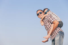 Dad and son in sunglasses playing in the park at the day time. People having fun outdoors.  Concept of friendly family Stock Image