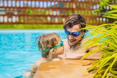 Dad and son in swimming Goggles have fun in the pool stock image